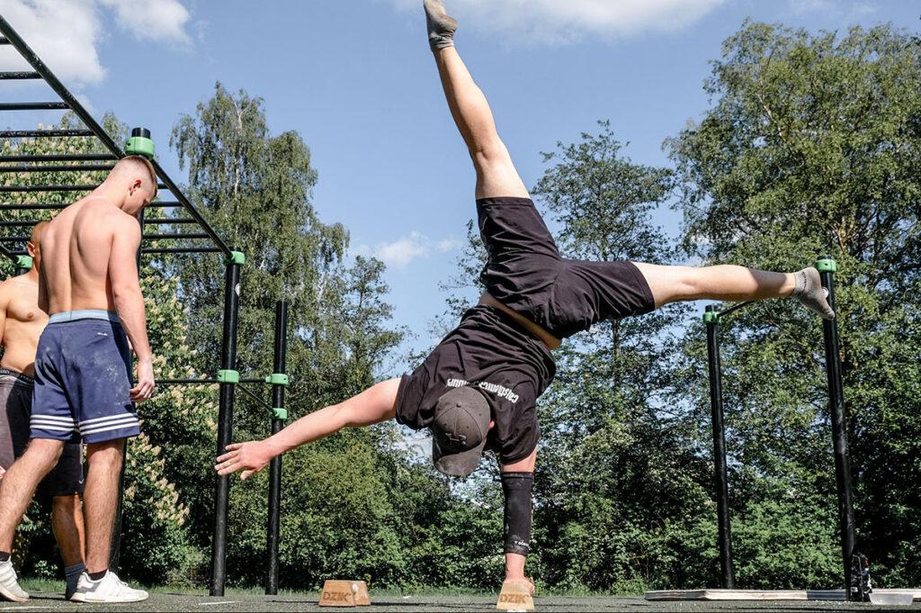 Ein Athlet macht im Calisthenics-Park einen einarmigen Handstand