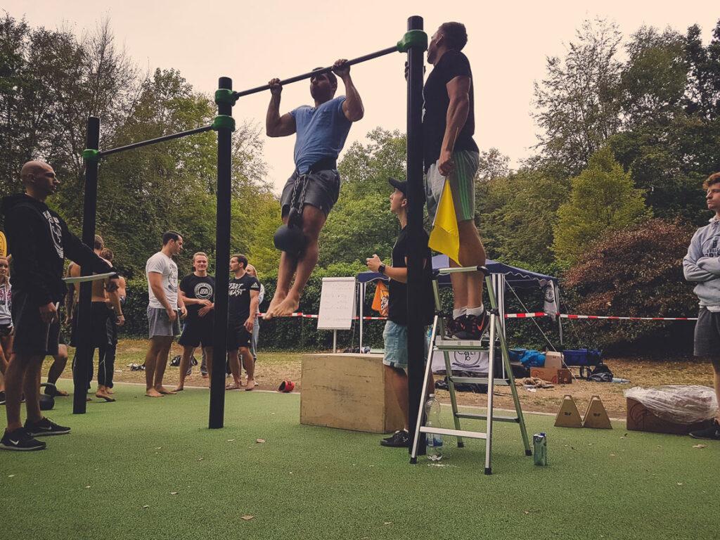 Athlet macht einen weighted Pull Up während eines Wettkampfs bei einer Parkeröffnung