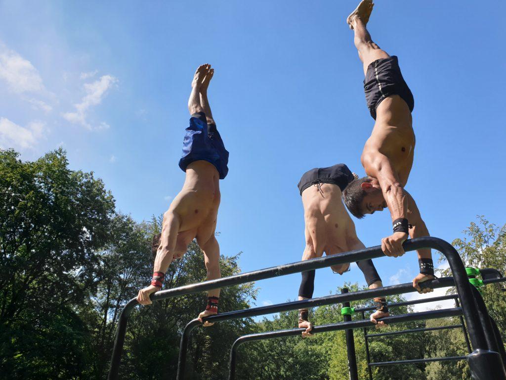 Drei Athleten machen einen Handstand auf einem Barren