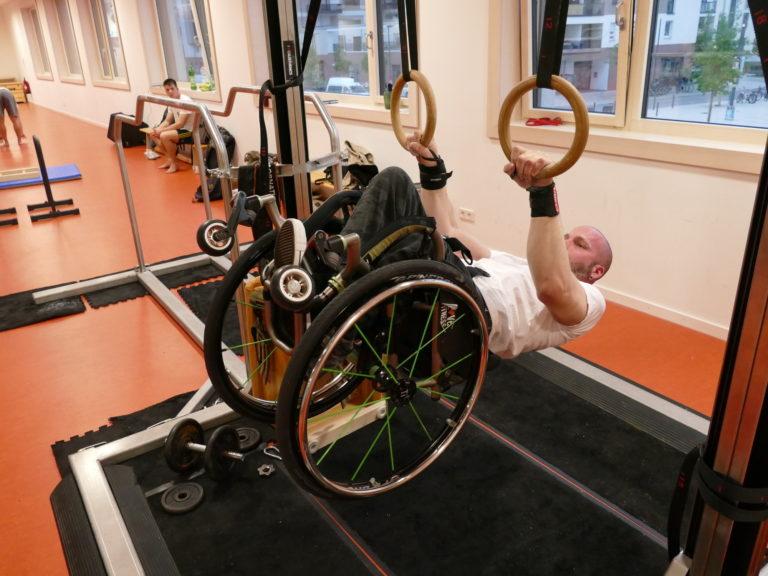Rollstuhlfahrer macht einen Frontlever an den Ringen