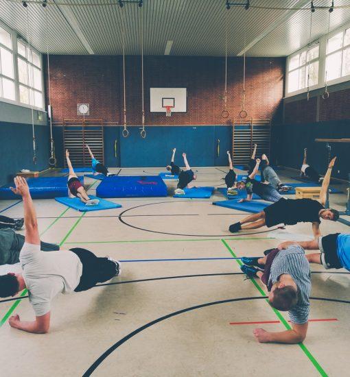 Eine Gruppe macht gemeinsam in einem Zirkel die seitliche Planke